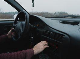 Personne au volant d'une voiture noire